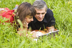 Couple with computer in grass Royalty Free Stock Photo