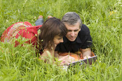 Couple with computer on grass Royalty Free Stock Image