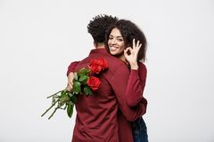 Couple Concept - Young african american couple huging each other and holding romantic red rose. Couple Concept - Young african american couple huging each other stock images
