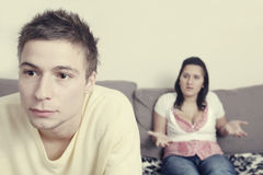 Couple conflict. A young couple is in a conflicting situation. The husband stares away while his wife is nagging in the background royalty free stock photography