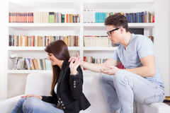 Couple in conflict arguing at home holding hands Stock Photo