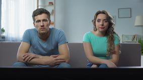 Couple in conflict watching tv silently ignoring each other, relationship crisis. Stock footage stock footage