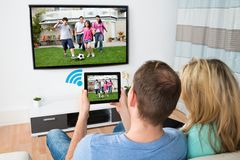 Couple connecting television and digital table with wifi Royalty Free Stock Image