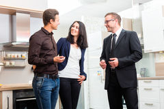 Couple consult salesman for domestic kitchen. Man and women consult salesman for domestic kitchen in studio or furniture store stock photography