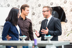Couple consulting salesman for domestic kitchen Stock Photos