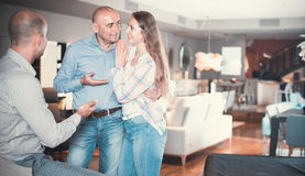 Couple is consulting with seller to choose new sofa stock photography