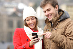 Couple consulting a smart phone in winter Stock Photo