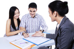 Couple consults with agent, signing paperwork Royalty Free Stock Images