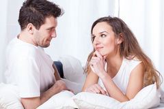 A couple contemplating in bed. A men and a women lying in bed and wondering Royalty Free Stock Images