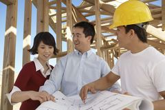Couple With Contractor At Construction Site Royalty Free Stock Photos