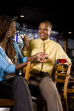 Couple conversing at a bar. Young African American couple sitting at a bar drinking and conversing Royalty Free Stock Image