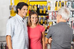 Couple Conversing With Man In Hardware Store Royalty Free Stock Photo