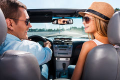 Couple in convertible. Beautiful young couple enjoying road trip in their convertible and looking at each other with smile Royalty Free Stock Image
