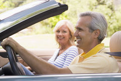 Couple in convertible car smiling Royalty Free Stock Photos