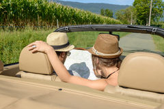 A couple in a convertible, look at a map Royalty Free Stock Photo