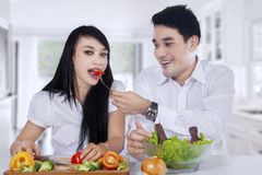 Couple cook and eat salad Royalty Free Stock Images