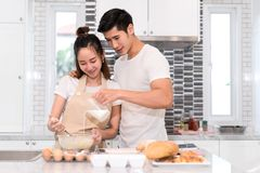 Couple cooking bakery in kitchen room, Young asian man and woman together royalty free stock images