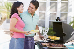 Couple Cooking On A Barbeque Stock Image