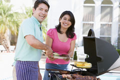 Couple Cooking On A Barbeque Royalty Free Stock Photos