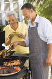 Couple Cooking On A Barbeque Stock Photo
