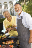 Couple Cooking On A Barbeque Royalty Free Stock Photo