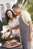 Couple Cooking On A Barbeque Stock Images