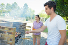 Couple cooking on barbeque. Couple cooking on a barbeque Royalty Free Stock Photography