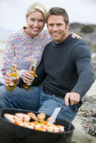 Couple Cooking Barbeque On A Beach Stock Image