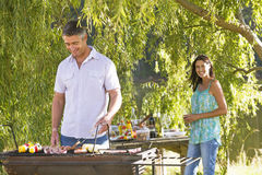 Couple Cooking Barbeque In Countryside Stock Images