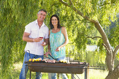 Couple Cooking Barbeque In Countryside Royalty Free Stock Photo