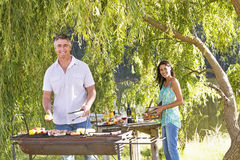 Couple Cooking Barbeque In Countryside Stock Photography