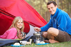 Couple Cooking Breakfast On Camping Holiday Stock Photos