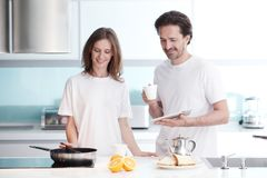 Couple cooking breakfast royalty free stock photography