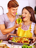 Couple cooking chicken at kitchen. Royalty Free Stock Photography