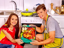 Couple cooking chicken at kitchen Stock Photo