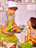 Couple cooking chicken at kitchen Royalty Free Stock Photos