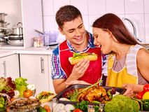 Couple cooking chicken at kitchen Stock Photography