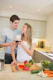 Couple cooking and clinking wine glasses Royalty Free Stock Photography