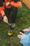 Couple cooking coffee on primus outdoors Royalty Free Stock Images