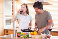 Couple cooking dinner while drinking wine Royalty Free Stock Photo