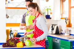 Couple cooking in domestic kitchen healthy food. Man and women preparing healthy meal in domestic kitchen at home Stock Images