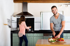 Couple Cooking In Domestic Kitchen royalty free stock photography