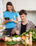 Couple cooking with electronic Book Stock Image