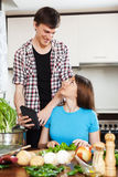 Couple cooking with electronic device Royalty Free Stock Photography