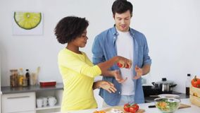 Couple cooking food and juggling tomatoes at home stock video footage