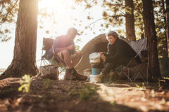 Couple cooking food outdoors on a camping trip. Senior couple cooking and making food outdoors on a camping trip. Mature men and women sitting outside the tent Royalty Free Stock Images