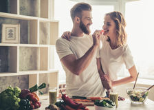 Couple cooking healthy food. Beautiful young couple is smiling while cooking healthy food in kitchen at home Stock Photo