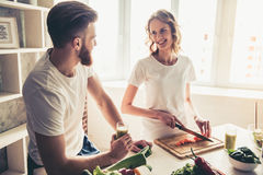 Couple cooking healthy food. Beautiful young couple is talking and smiling while cooking healthy food in kitchen at home Royalty Free Stock Image