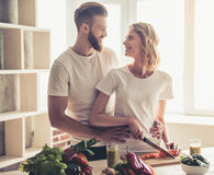 Couple cooking healthy food. Beautiful young couple is talking and smiling while cooking healthy food in kitchen at home Royalty Free Stock Images
