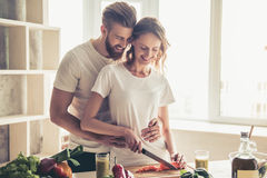 Couple cooking healthy food. Beautiful young couple is talking and smiling while cooking healthy food in kitchen at home Stock Image